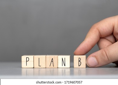Wooden cubes with the word Plan B on grey background and human finger, business concept background close-up
