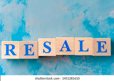 Wooden cubes with word RESALE on blue table. Cubes with blue letters.