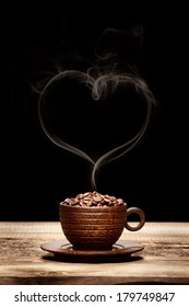 Wooden cup with beans and heart-shaped smoke on dark background