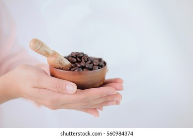 wooden cup of coffee seed in hand and white background. raw ingredient food