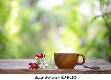 Wooden cup and flowers on wooden table