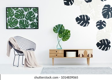 Wooden cupboard with monstera leaves in vase next to chair in flat interior with green poster