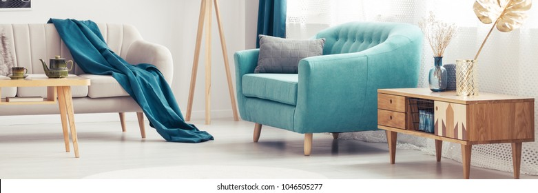 Wooden cupboard next to turquoise armchair in living room interior with blue blanket on sofa