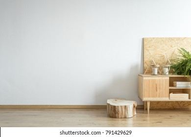 Wooden cupboard standing by a tree trunk in an empty room interior