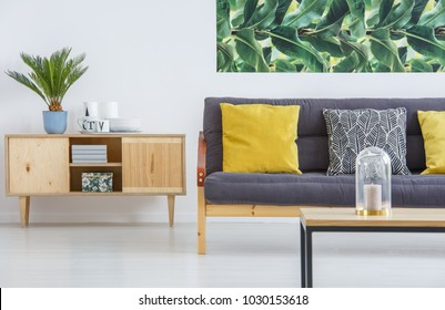 Wooden cupboard standing next to black sofa with cushions and botanical poster on the wall in a living room interior
