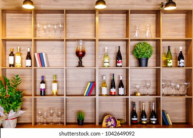 wooden cupboard with wine, glasses and flowers