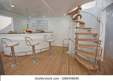 Wooden curved spiral staircase and bar area on sundeck of large luxury motor yacht