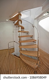 Wooden curved spiral staircase on sundeck area of large luxury motor yacht