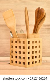 Wooden cutlery, bamboo Spatulas and spoons in wooden basket on beige kitchen countertop. Beige kitchen interior with wooden spoons. Eco-friendly materials. Space for text. selective focus