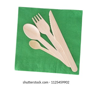 Wooden cutlery, fork, spoon, knife with green paper napkin isolated on white.