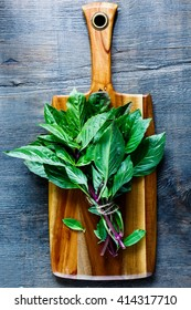 Wooden cutting board with bunch of thai basil on dark rustic background, top view. Simple food concept.