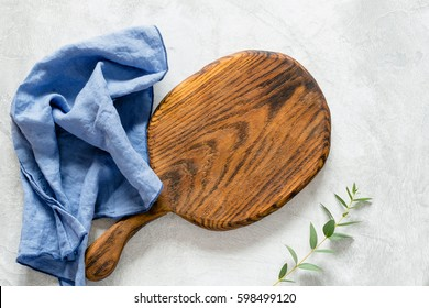 Wooden cutting board for cooking, blue kitchen napkin and olive branch on a gray stone background. Top view, copy space for text