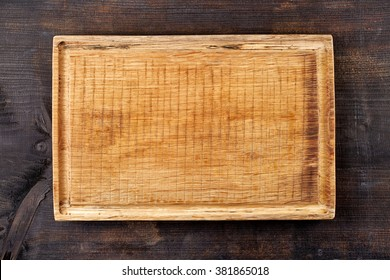 Wooden cutting board on black wooden table, top view