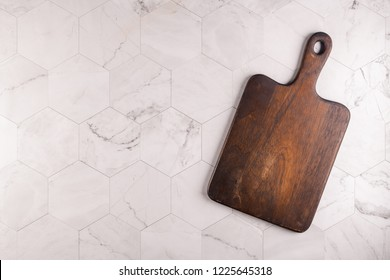Wooden cutting board on a light gray hexagonal marble tiles background. Top view. Copy space for text.