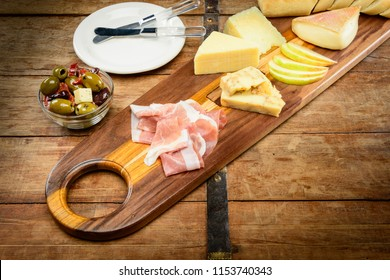 Wooden cutting board with Prosciutto Ham, Golden Delicious Apple, Green Olives, Kalamata Olives, Smoked Gouda and Brie