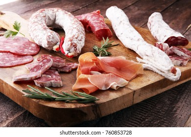 Wooden cutting board with prosciutto, salami, sausages  and  rosemary