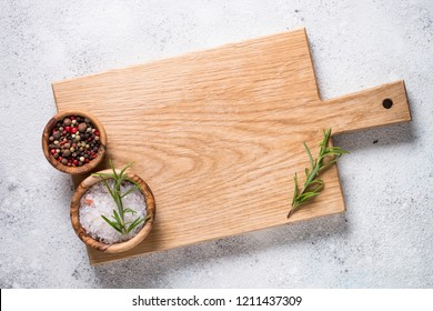 Wooden cutting board with sea salt and pepper on white stone table. Top view copy space.
