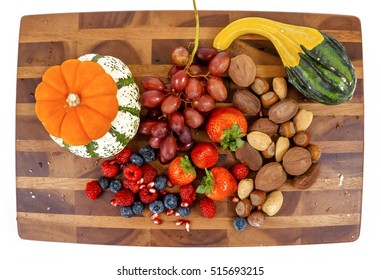 Wooden cutting board with strawberries, blueberries, raspberries, pomegranate seeds, nuts, almonds, walnuts, pecans, pumpkins and a squash.