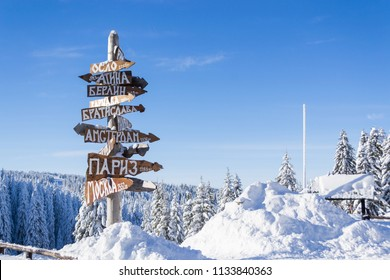 Wooden cyrillic sign of world capitals in the mountains. Translation top to bottom: Rome, Oslo, Athens, Berlin, Warsaw, Bratislava, Madrid, Amsterdam, Bucharest, Paris, Moscow.