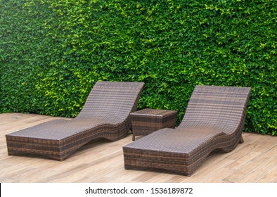 Wooden daybed place on wooden floor beside swimming pool in the resort with green bush in background.