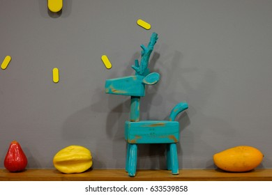 Wooden dear with fake fruits in gray background