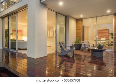 Wooden deck / balcony at night with furniture and open doors leading to inside.