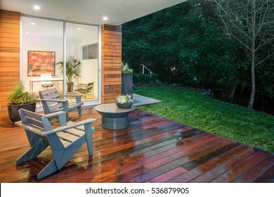 Wooden deck / balcony at night with furniture looking inside.