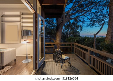 Wooden deck / balcony at night with open doors leading to living room.