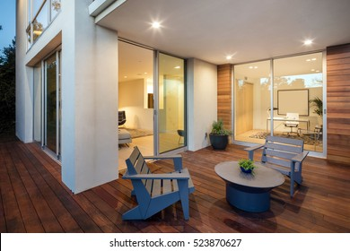 Wooden deck / balcony at night with open doors leading to living