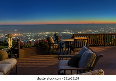 Wooden deck / balcony at night with seating arrangement.