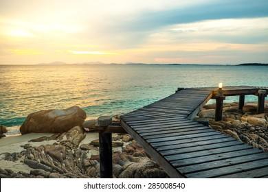Holzdeck, Holzbrücke, mit Sonnenuntergang, tropischer Strand auf der Insel Munnork, Rayong, Thailand