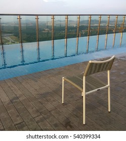 Wooden deck chair and infinity swimming pool