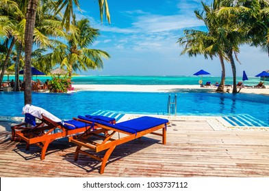 Wooden deck chairs with blue pillows above the pool. In the background, the azure water of the ocean and a sandy beach with palm trees.