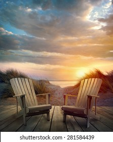 Wooden deck with chairs, sand dunes and ocean at sunset