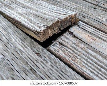 Wooden deck floor boards coming up that are old, warped and weathered, needing to be nailed and repaired