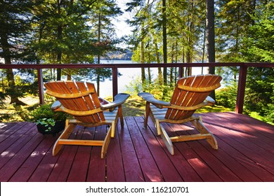 Wooden deck at forest cottage with Adirondack chairs