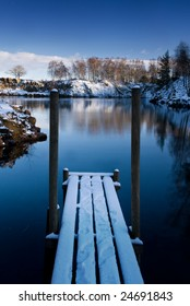 Wooden deck on the shore of a small lake in winter (Sweden).