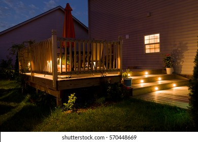 Wooden deck and patio of family home at night.