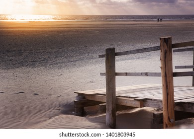 wooden deck in the sand by the ocean at sunset