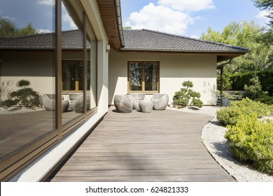 Wooden deck of a terrace by a white suburban villa