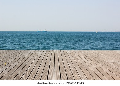 wooden deck waterfront sea shoreline background texture and water surface with small waves with horizon line, wallpaper pattern, copy space