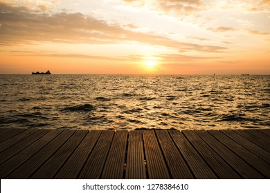 wooden deck waterfront shoreline and sea landscape horizon with ship in romantic sunset evening orange lighting time