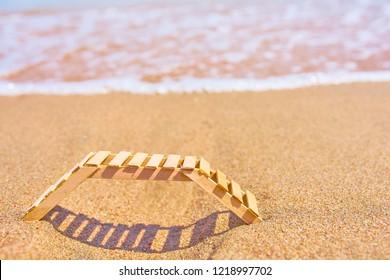 Wooden deckchair on a tropical sand beach. Empty wooden chairs or deckchairs on wood shore overlooking scenic calm river.