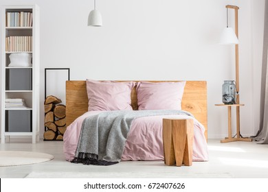 Wooden decor spacious bedroom with pink bedding and white walls