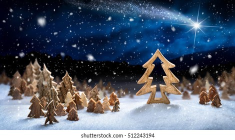 Wooden decoration arranged in snow, forming a fantasy forest night landscape with a shooting star, ideal for Christmas or winter