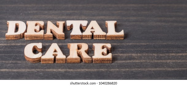 Wooden 'Dental Care' words over dark table top
