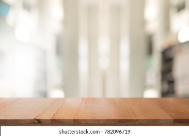 Wooden desk with Abstract blurred livingroom decoration interior for background.