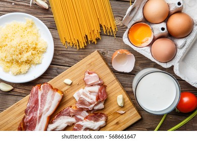 Wooden desk with bacon, parmesan, spaghetti and eggs