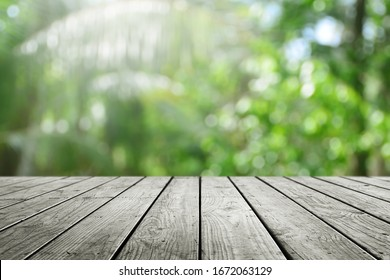 Wooden desk and blurred nature bokeh background.