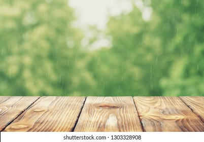 wooden desk and blurred summer background, forest in the rain